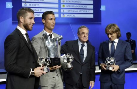 "Real Madrid 's Sergio Ramos ""Defender of the saison 2016-2017"", left, Real Madrid's Cristiano Ronaldo of Portugal ""Forward of the saison 2016-2017"", second left, Real Madrid's Luka Modric, right, ""Midfielder of the saison 2016-2017"", hold their trophies , as they pose with Real Madrid's president Florentino Perez, after the UEFA Champions League draw, at the Grimaldi Forum, in Monaco, Thursday, Aug. 24, 2017. (AP Photo/Claude Paris)"