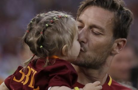 Roma's Francesco Totti kisses her daughter Isabel as he salutes his fans after an Italian Serie A soccer match between Roma and Genoa at the Olympic stadium in Rome, Sunday, May 28, 2017. Francesco Totti is playing his final match with Roma against Genoa after a 25-season career with his hometown club. (AP Photo/Alessandra Tarantino)