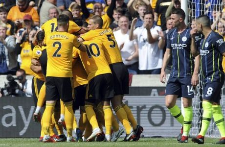 Wolverhampton Wanderers players celebrate after Willy Boly scored the opening goal during the English Premier League soccer match between Wolverhampton Wanderers and Manchester City at the Molineux Stadium in Wolverhampton, England, Saturday, Aug. 25, 2018. (AP Photo/Rui Vieira)