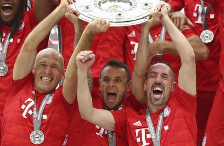 Front from left, Bayern's Arjen Robben, Rafinha and Franck Ribery lift the trophy to celebrate Bayern's 7th straight Bundesliga title after the German Soccer Bundesliga match between FC Bayern Munich and Eintracht Frankfurt in Munich, Germany, Saturday, May 18, 2019. (AP Photo/Matthias Schrader)