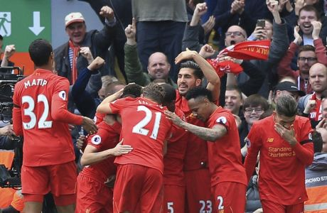 Liverpool's Divock Origi is mobbed by his teammates after scoring his side's third goal, during the English Premier League soccer match between Liverpool and Everton, at Anfield, in Liverpool, England, Saturday April 1, 2017. (Peter Byrne/PA via AP)