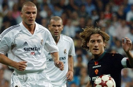 Roma's Francesco Totti, right, gets past Real Madrid's English player David Beckham, left, and Zinedine Zidane of France during their Champions League soccer match in Madrid Tuesday, Sept. 28, 2004. (AP Photo/Paul White)