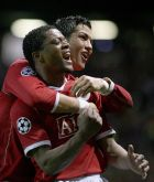 Manchester United's Patrice Evra, left, celebrates with Cristiano Ronaldo after scoring the seventh goal against Roma during their Champions League quarter final second-leg soccer match at Old Trafford Stadium, Manchester, England, Tuesday April 10, 2007. (AP Photo/Jon Super)