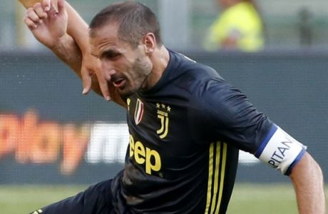 Juventus' Giorgio Chiellini and Chievo's Mariusz Stepinski , left, vie for the ball during the Serie A soccer match between Chievo Verona and Juventus, at the Bentegodi Stadium in Verona, Italy, Saturday, Aug. 18, 2018. (AP Photo/Antonio Calanni)