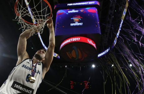 Slovenia's Aleksej Nikolic cuts the net off the basket after defeating Serbia in the Eurobasket European Basketball Championship final match in Istanbul, Sunday, Sept. 17. 2017. (AP Photo/Thanassis Stavrakis)