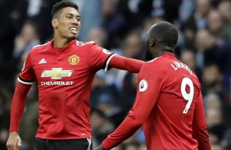 Manchester United's Chris Smalling, left, celebrates after scoring his side's third goal during the English Premier League soccer match between Manchester City and Manchester United at the Etihad Stadium in Manchester, England, Saturday April 7, 2018. (AP Photo/Matt Dunham)