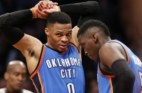 Oklahoma City Thunder guard Russell Westbrook (0) stretches his arms after drawing a foul in the second half of an NBA basketball game, Tuesday, March 14, 2017, in New York. Westbrook had 25 points, 19 assists and 11 rebounds as the Thunder defeated the Nets 122-104. Oklahoma City Thunder guard Victor Oladipo (5) is at right. (AP Photo/Kathy Willens)