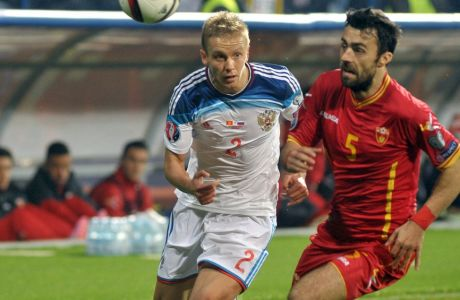 Russia's Igor Smolnikov, left, challenges with Montenegro's Marko Basa during the Euro 2016 Group G qualifying soccer match between Montenegro and Russia, at the City Stadium in Podgorica, Montenegro, Friday, March 27, 2015. (AP Photo/Risto Bozovic)