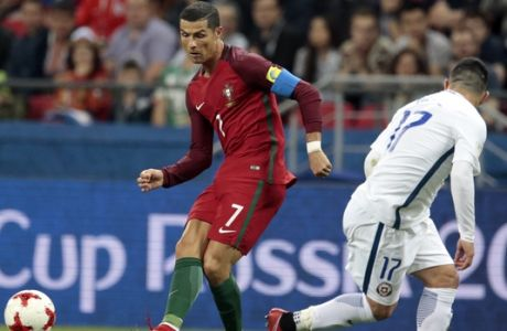 Portugal's Cristiano Ronaldo left, sends the ball past Chile's Gary Medel during the Confederations Cup, semifinal soccer match between Portugal and Chile, at the Kazan Arena, Russia, Wednesday, June 28, 2017. (AP Photo/Ivan Sekretarev)