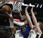 Denver Nuggets guard Malik Beasley (25) drives to the basket between San Antonio Spurs center LaMarcus Aldridge (12) and center Jakob Poeltl (25) during the first half of Game 6 of an NBA basketball playoff series, Thursday, April 25, 2019, in San Antonio. (AP Photo/Eric Gay)