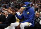 Golden State Warriors guard Stephen Curry, back, confers with forward Kevin Durant as they watch from the bench late in the second half of an NBA basketball game against the Denver Nuggets, Tuesday, Jan. 15, 2019, in Denver. The Warriors won 142-111. (AP Photo/David Zalubowski)