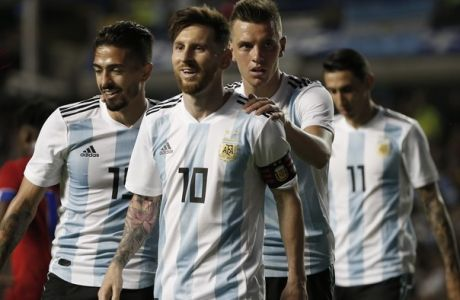 Argentina's Manuel Lanzini, left, Giovanni Lo Celso, second right, and Angel Di Maria, right, congratulate teammate Lionel Messi, second left, after his hat trick during a friendly soccer match between Argentina and Haiti at the Bombonera stadium in Buenos Aires, Argentina, Tuesday, May 29, 2018. (AP Photo/Natacha Pisarenko)