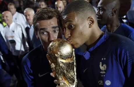 France's Kylian Mbappe, right, and and Antoine Griezmann kiss the World Cup trophy during a ceremony following the UEFA Nations League soccer match between France and The Netherlands at the Stade de France stadium in Saint-Denis, outside Paris, France, Sunday, Sept. 9, 2018. (AP Photo/Christophe Ena)
