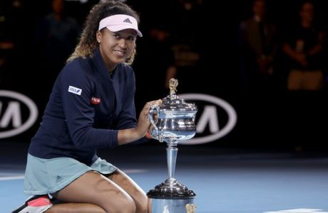 Japan's Naomi Osaka poses with her trophy after defeating Petra Kvitova of the Czech Republic in the women's singles final at the Australian Open tennis championships in Melbourne, Australia, Saturday, Jan. 26, 2019. (AP Photo/Mark Schiefelbein)