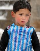 In this Friday, Jan. 29, 2016 photo,  Murtaza Ahmadi, a five-year-old Afghan Lionel Messi fan plays football near his home, in the Jaghori district of Ghazni in Afghanistan. The Afghan Football Federation plans to set up a meeting between  Messi and Ahmadi who became an Internet sensation when photos circulated of him wearing an improvised Messi shirt made from a plastic bag. (AP Photo)