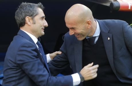 Barcelona coach Ernesto Valverde, left and Real Madrid's coach Zinedine Zidane greet each other before the start of the Spanish La Liga soccer match between Real Madrid and Barcelona at the Santiago Bernabeu stadium in Madrid, Spain, Saturday, Dec. 23, 2017. (AP Photo/Paul White)