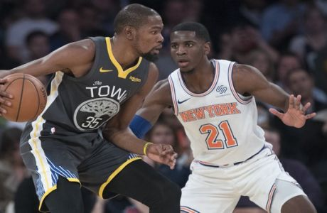 New York Knicks guard Damyean Dotson (21) guards Golden State Warriors forward Kevin Durant (35) during the second half of an NBA basketball game, Friday, Oct. 26, 2018, at Madison Square Garden in New York. The Warrior won 128-100. (AP Photo/Mary Altaffer)