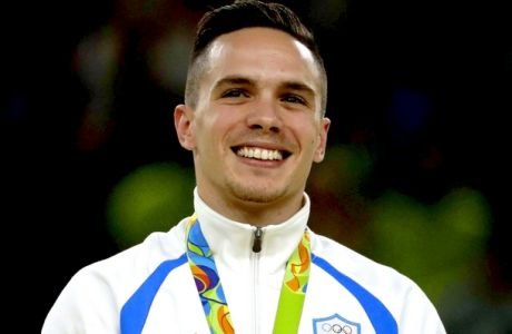 Greece's Eleftherios Petrounias, gold medallist, stands on the podium during the medal ceremony for the artistic gymnastics men's rings final at the 2016 Summer Olympics in Rio de Janeiro, Brazil, Monday, Aug. 15, 2016. (AP Photo/Julio Cortez)
