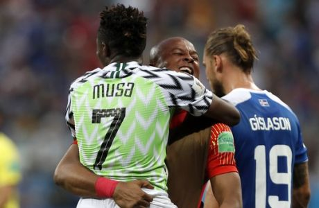 Nigeria's Ahmed Musa, left, is embraced by a teammate as they celebrate their 2-0 win over Iceland in their group D match at the 2018 soccer World Cup in the Volgograd Arena in Volgograd, Russia, Friday, June 22, 2018. (AP Photo/Darko Vojinovic)