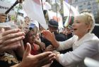 Former Ukrainian Prime Minister Yulia Tymoshenko greets her supporters outside the Pecherskiy District Court in Kiev, Monday, July 18, 2011. The Ukrainian security service says it has opened a criminal investigation into the activities of an energy company once headed by former Prime Minister Yulia Tymoshenko. Tymoshenko, the country's top opposition leader, is already on trial on charges she abused her office in signing a natural gas import deal with Russia in 2009. Tymoshenko denies the accusations and says the trial is an attempt by President Viktor Yanukovych to bar her from politics. (AP Photo/Sergei Chuzavkov)