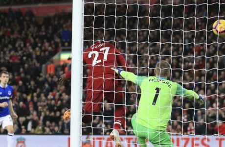 Liverpool forward Divock Origi, center, scores his side's first goal during the English Premier League soccer match between Liverpool and Everton at Anfield Stadium in Liverpool, England, Sunday, Dec. 2, 2018. (AP Photo/Jon Super)