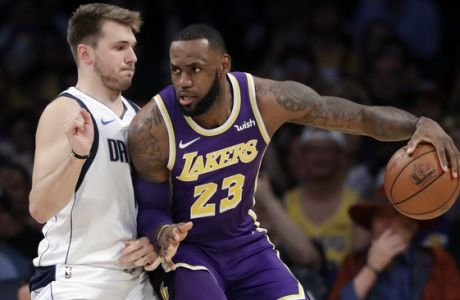 Los Angeles Lakers' LeBron James (23) is defended by Dallas Mavericks' Luka Doncic during the first half of an NBA basketball game Wednesday, Oct. 31, 2018, in Los Angeles. (AP Photo/Marcio Jose Sanchez)