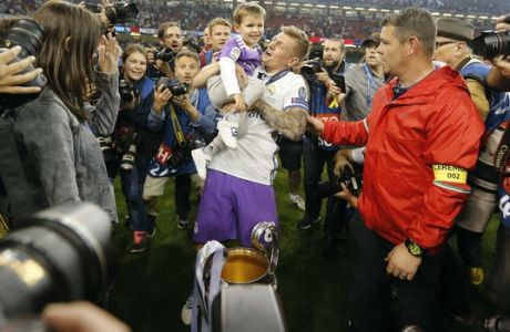 Real Madrid's Toni Kroos lifts his son as he celebrates at the end of the Champions League soccer final between Juventus and Real Madrid at the Millennium Stadium in Cardiff, Wales, Saturday, June 3, 2017. Real won the match 4-1. (AP Photo/Frank Augstein)
