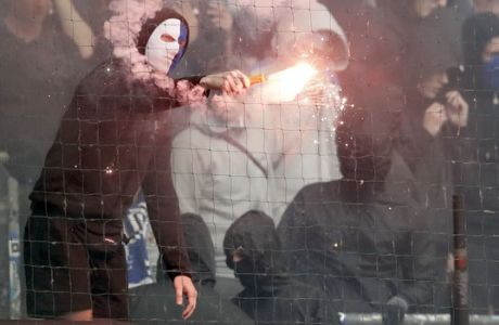 A Hamburg fan lights fireworks when his team relegates for the first time in Geran Bundesliga history during the German Bundesliga soccer match between Hamburger SV and VfL Borussia Moenchengladbach in Hamburg, Germany, Saturday, May 12, 2018. (AP Photo/Michael Sohn)