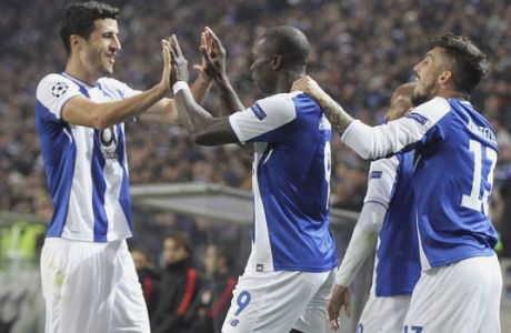 Porto's Vincent Aboubakar, center, celebrates with Ivan Marcano, left, after scoring his side's second goal during the Champions League group G soccer match between FC Porto and AS Monaco at the Dragao stadium in Porto, Portugal, Wednesday, Dec. 6, 2017. (AP Photo/Luis Vieira)
