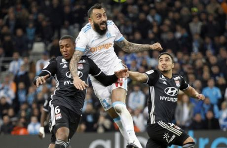 Marseille's Konstantinos Mitroglou, center, challenges for the ball with Lyon's Marcelo, left, and Rafael Da Silva during the League One soccer match between Marseille and Lyon at the Velodrome stadium, in marseille, southern France , Sunday, March 18, 2018. (AP Photo/Claude Paris)