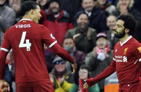 Liverpool's Mohamed Salah, right, celebrates with Virgil van Dijk after scoring his side's first goal during the English Premier League soccer match between Liverpool and Tottenham Hotspur at Anfield, Liverpool, England, Sunday, Feb. 4, 2018. (AP Photo/Rui Vieira)