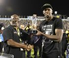"""Jamaica's Usain Bolt receives a special award from his coach, Glen Mills, before competing in the """"Salute to a Legend"""" 100 meters during the Racers Grand Prix at the national stadium in Kingston, Jamaica, Saturday, June 10, 2017. Bolt started his final season with his last race on Jamaican soil and plans to retire from track and field after the 2017 London World Championships in August. (AP Photo/Bryan Cummings)"""