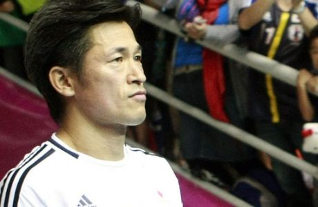 Kazuyoshi Miura of Japan walks into the arena is watched by cheering Japanese fans, prior to the  Futsal World Cup second round match against Ukraine, in Bangkok, Thailand, Sunday, Nov. 11, 2012. (AP Photo/Apichart Weerawong)
