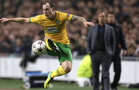 Celtic's Anthony Stokes accepts a high ball as Ajax coach Frank de Boer, rear, watches,  during the Champions League Group H soccer match between Ajax Amsterdam and Celtic Glasgow at ArenA stadium in Amsterdam, Netherlands, Wednesday, Nov. 6, 2013. (AP Photo/Peter Dejong)