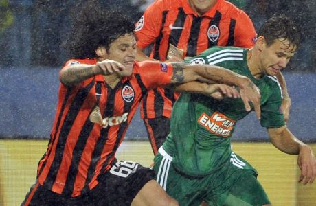 Rapid's Louis Schaub, right, and Shakhtar's Marcio Azevedo challenge for the ball during their Champions League play-off first leg soccer match between SK Rapid Wien and FC Shakhtar Donetsk in Vienna, Austria, Wednesday, Aug. 19, 2015. (AP Photo/Hans Punz)
