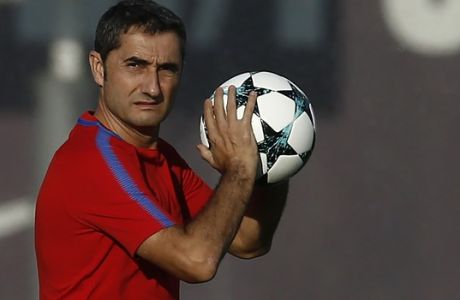 FC Barcelona's coach Ernesto Valverde holds a ball as he attends a training session at the Sports Center FC Barcelona Joan Gamper in Sant Joan Despi, Spain, Tuesday, Oct. 17, 2017. FC Barcelona will play against Olympiacos in a Champions League Group D soccer match on Wednesday. (AP Photo/Manu Fernandez)