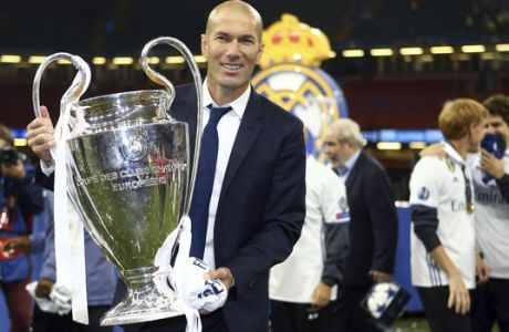 Real Madrid's head coach Zinedine Zidane celebrates with the trophy at the end of the Champions League soccer final between Juventus and Real Madrid at the Millennium Stadium in Cardiff, Wales, Saturday, June 3, 2017. Real won the match 4-1. (AP Photo/Dave Thompson)
