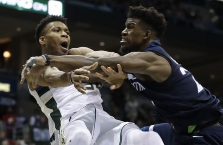Milwaukee Bucks' Giannis Antetokounmpo is fouled by Minnesota Timberwolves' Jimmy Butler during the second half of an NBA basketball game Thursday, Dec. 28, 2017, in Milwaukee. The Bucks won 102-96. (AP Photo/Morry Gash)