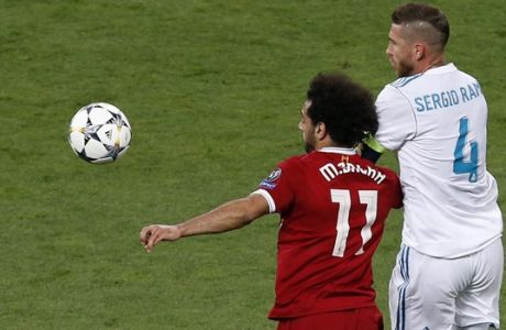 Liverpool's Mohamed Salah, left, and Real Madrid's Sergio Ramos challenge for the ball during the Champions League Final soccer match between Real Madrid and Liverpool at the Olimpiyskiy Stadium in Kiev, Ukraine, Saturday, May 26, 2018. (AP Photo/Darko Vojinovic)