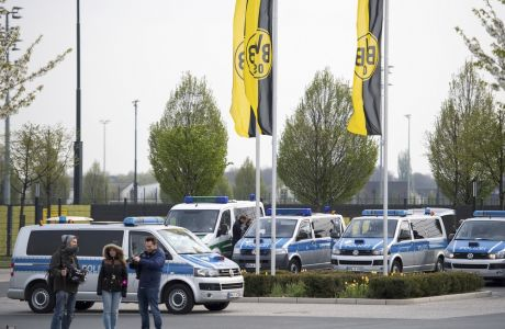 Police cars park outside the training grounds of Borussia Dortmund in Dortmund, Germany, Wednesday, April 12, 2017, the day after the team bus was damaged in an explosion which injured a player and a police officer. (Marius Becker/dpa via AP)