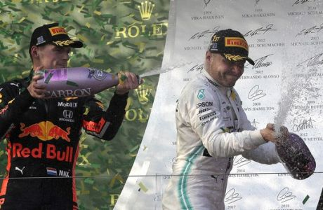 Mercedes driver Valtteri Bottas of Finland, right, is sprayed with champagne by Red Bull driver Max Verstappen of the Netherlands as they celebrate after the Australian Formula 1 Grand Prix in Melbourne, Australia, Sunday, March 17, 2019. Bottas won ahead of teammate Lewis Hamilton of Britain while Verstappen placed third. (AP Photo/Rick Rycroft)