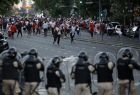 Argentina River Plate fans clash with riot police outside the Antonio Vespucio Liberti stadium prior the final soccer match of the Copa Libertadores between River Plate and Boca Juniors, in Buenos Aires, Argentina, Saturday, Nov. 24, 2018. The match has been rescheduled after the bus carrying the Boca Juniors players was attacked by River Plate fans, injuring several players. The match will be played on Sunday. (AP Photo/Sebastian Pani)