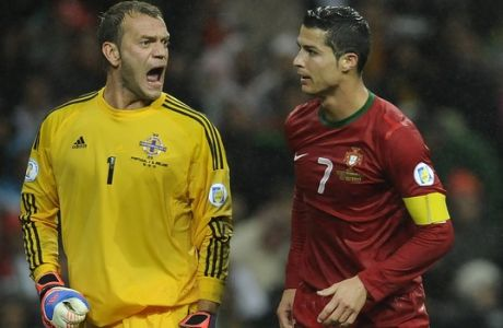 Northern Ireland's goalkeeper Roy Carroll, left, reacts as Portugal's Cristiano Ronaldo walks past during their World Cup Group F qualifying soccer match at the Dragao Stadium in Porto, Portugal, Tuesday Oct. 16, 2012. The match ended in a 1-1 draw.(AP Photo/Paulo Duarte)