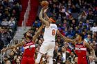 New York Knicks forward Michael Beasley (8) shoots over Washington Wizards forward Markieff Morris (5) and Washington Wizards forward Kelly Oubre Jr. (12) in the second half of an NBA basketball game, Sunday, March 25, 2018, in Washington. (AP Photo/Andrew Harnik)