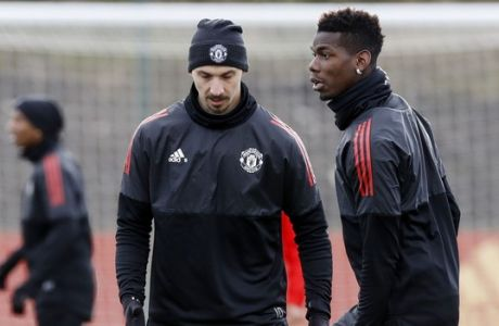 Manchester United's Paul Pogba, right, and Zlatan Ibrahimovic attend a training session ahead of Wednesday's Champions League, round of 16 first-leg soccer match against Sevilla, at the AON Training Complex, Carrington, England, Tuesday, Feb. 20, 2018.  (Martin Rickett/PA via AP)