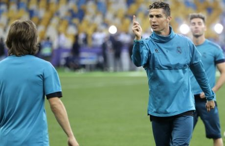 Real Madrid's Cristiano Ronaldo gestures at Luka Modric, left, during a training session at the Olimpiyskiy Stadium in Kiev, Ukraine, Friday, May 25, 2018 ahead of the Champions League final soccer match between Real Madrid and Liverpool on Saturday May 26. (AP Photo/Matthias Schrader)