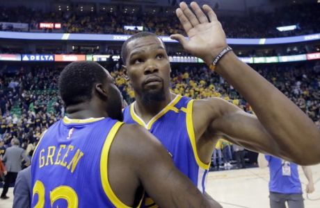 Golden State Warriors' Kevin Durant, right, receives a hug from teammate Draymond Green (23) following Game 3 of the NBA basketball second-round playoff series against the Utah Jazz, Saturday, May 6, 2017, in Salt Lake City. (AP Photo/Rick Bowmer)