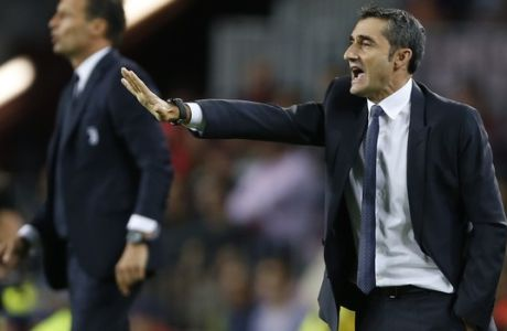 Barcelona coach Ernesto Valverde, right, and Juventus coach Massimiliano Allegri, left, gesture during a Champions League group D soccer match between FC Barcelona and Juventus at the Camp Nou stadium in Barcelona, Spain, Tuesday, Sept. 12, 2017. (AP Photo/Francisco Seco)