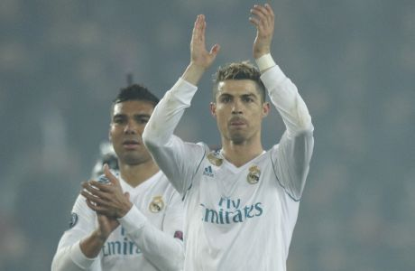 Real Madrid's scorers Casemiro, left, and Cristiano Ronaldo wave to their fans after the round of 16, 2nd leg Champions League soccer match between Paris Saint-Germain and Real Madrid at the Parc des Princes Stadium in Paris, Tuesday, March 6, 2018. Real Madrid won 2-1. (AP Photo/Francois Mori)
