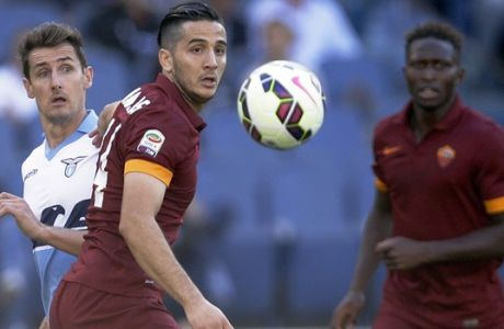 Lazio's Miroslav Klose, left, and Roma's Kostas Manolas, center, eye the ball during a Serie A soccer match between Lazio and Roma at Rome's Olympic Stadium, Monday, May 25, 2015. (AP Photo/Gregorio Borgia)